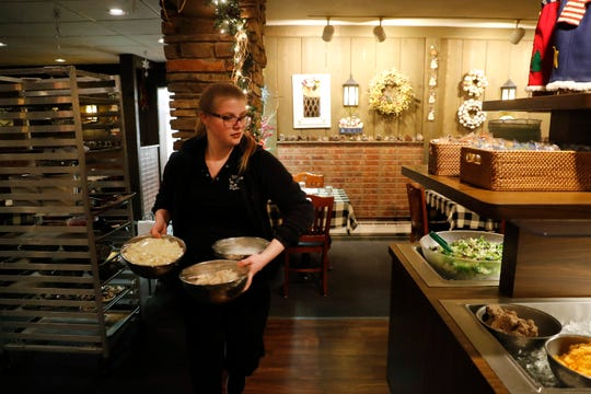 Anita Ditter, an employee at Roepke's Village Inn, prepares the salad bar on Dec. 12.