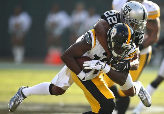 Pittsburgh Steelers wide receiver James Washington (13) is tackled by Oakland Raiders defensive back Rashaan Melvin (22) during the first half in Oakland, Calif., Sunday, Dec. 9, 2018.