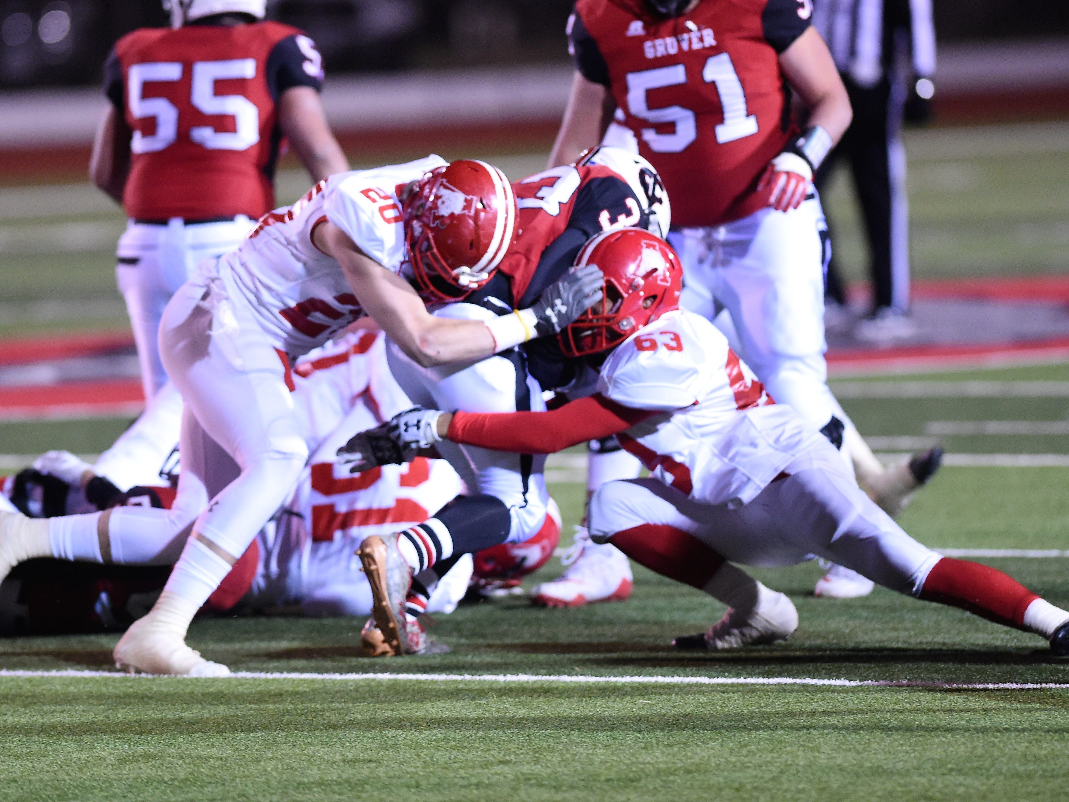 Albany's Ryan Hill (20) and Gregori Mikeska (63) sandwich Gruver's Brice McLaughlin (33) in the Class 2A Division II state semifinal at Sherwood Memorial Bulldog Stadium in Plainview on Thursday, Dec. 13, 2018.