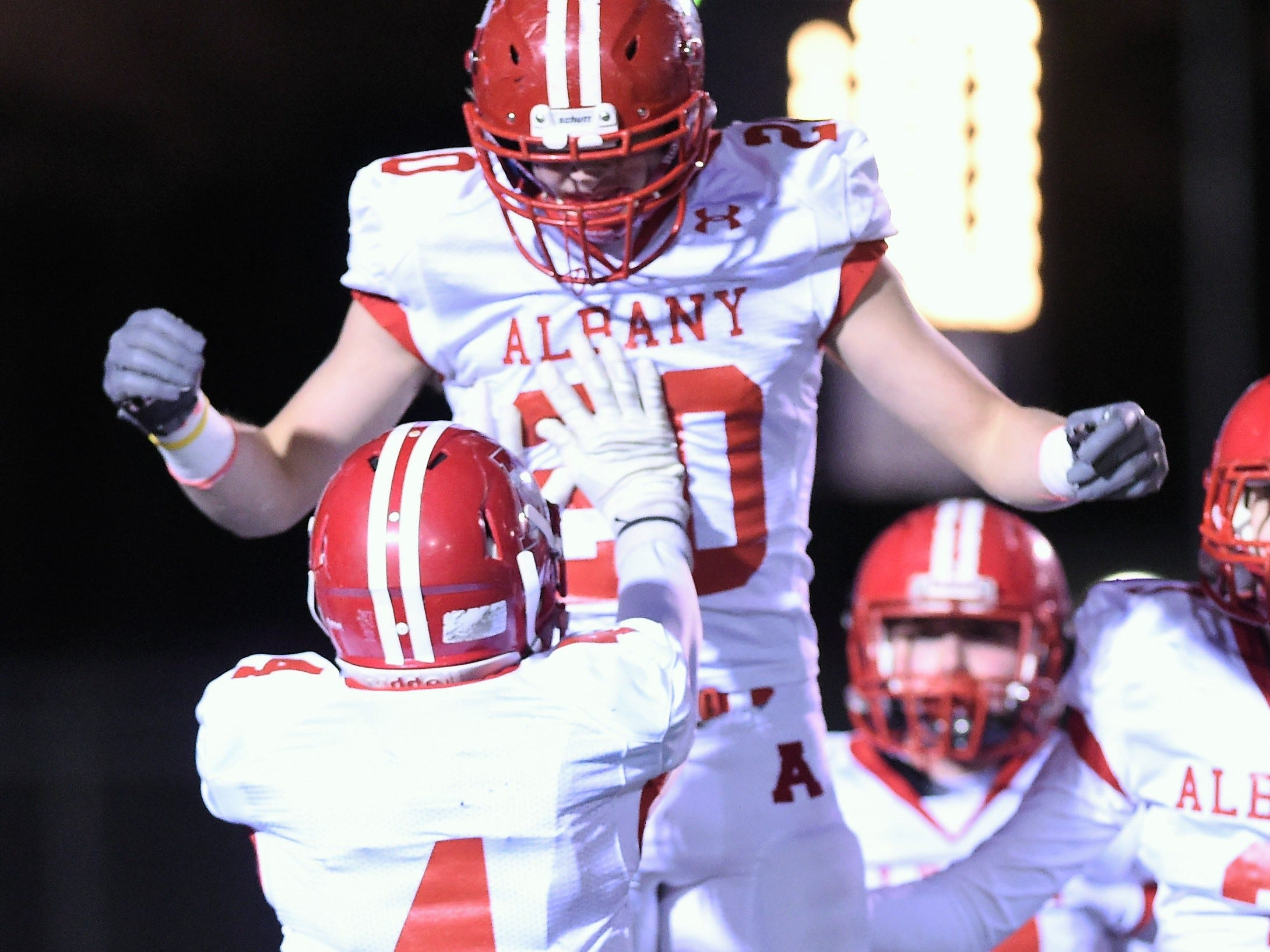 Albany's Ben West (4) picks up Ryan Hill (20) after a defensive touchdown against Gruver in the Class 2A Division II state semifinal at Sherwood Memorial Bulldog Stadium in Plainview on Thursday, Dec. 13, 2018.