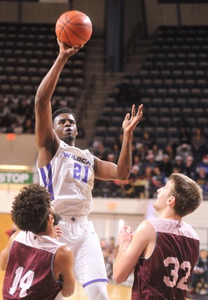 ACU's Jalone Friday (21) shoots over a pair of Schreiner defenders. ACU beat the Mountaineers 93-53 on Dec. 8, 2018, at Moody Coliseum.