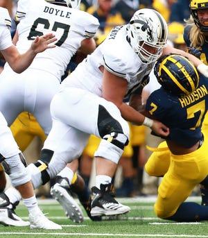 Western Michigan center John Keenoy blocks Michigan linebacker Khaleke Hudson (7) at Michigan Stadium on September 8, 2018 in Ann Arbor, Michigan.