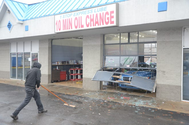 Workers sweep glass after a crash Friday, Dec. 14, 2018 at One Stop Express Lube in Battle Creek.