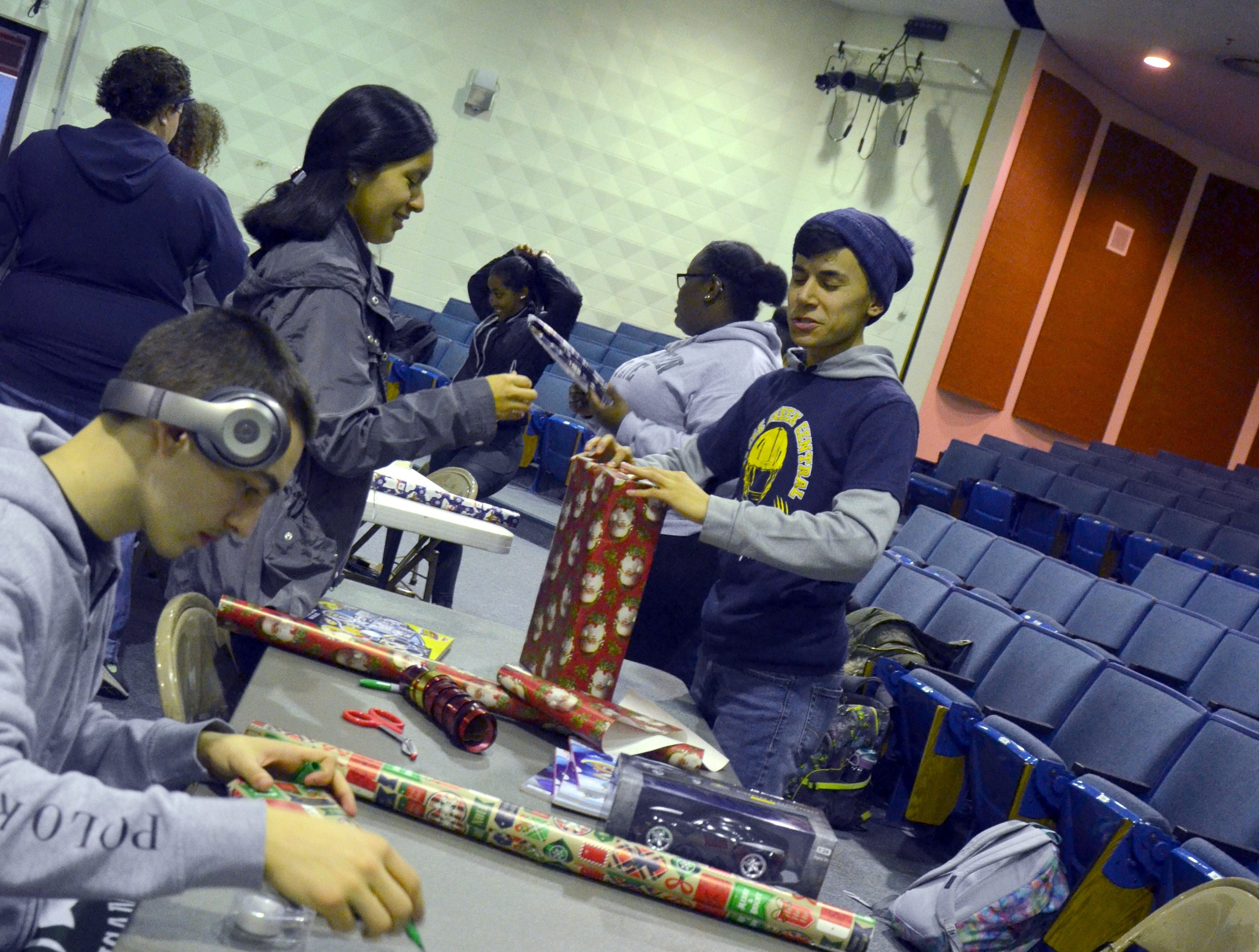 Battle Creek Central High School students wrap presents on Friday at the McQuiston Center.