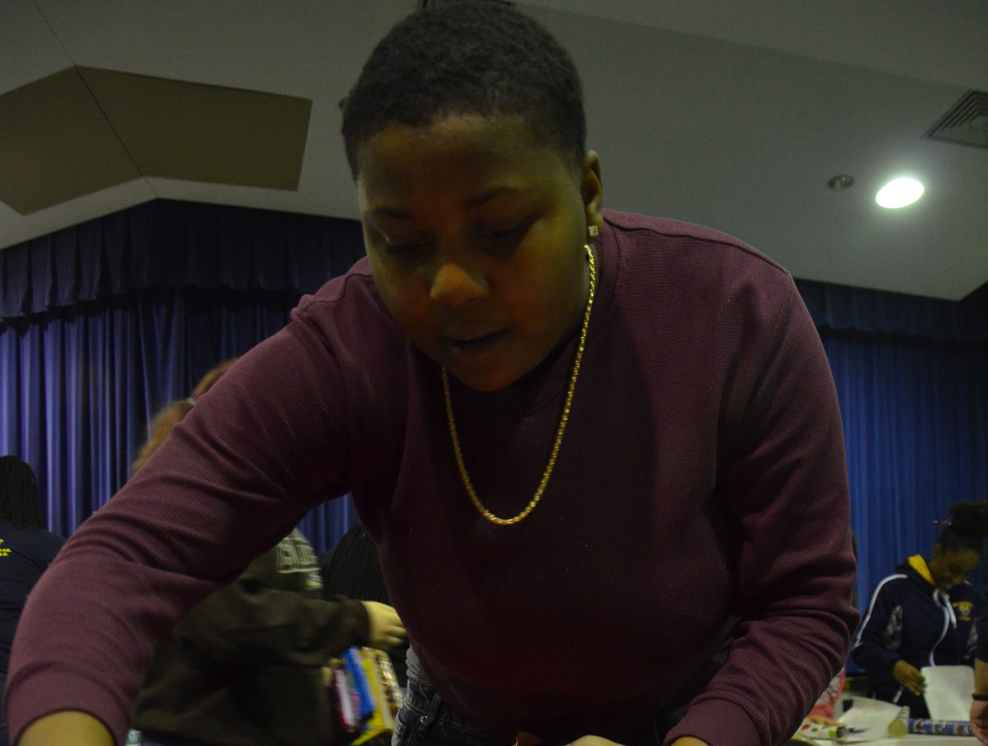 Julionna Hoover, 12th grade, cuts paper to wrap a present on Friday at Battle Creek Central High School.