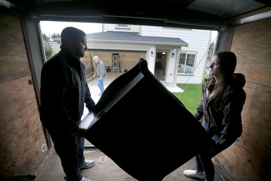 Brandon and Jessica Johnson move furniture to their new home at the opening ceremony of the Maple Lane Group One Kitsap Housing development in Kington on Friday, December 14, 2018.