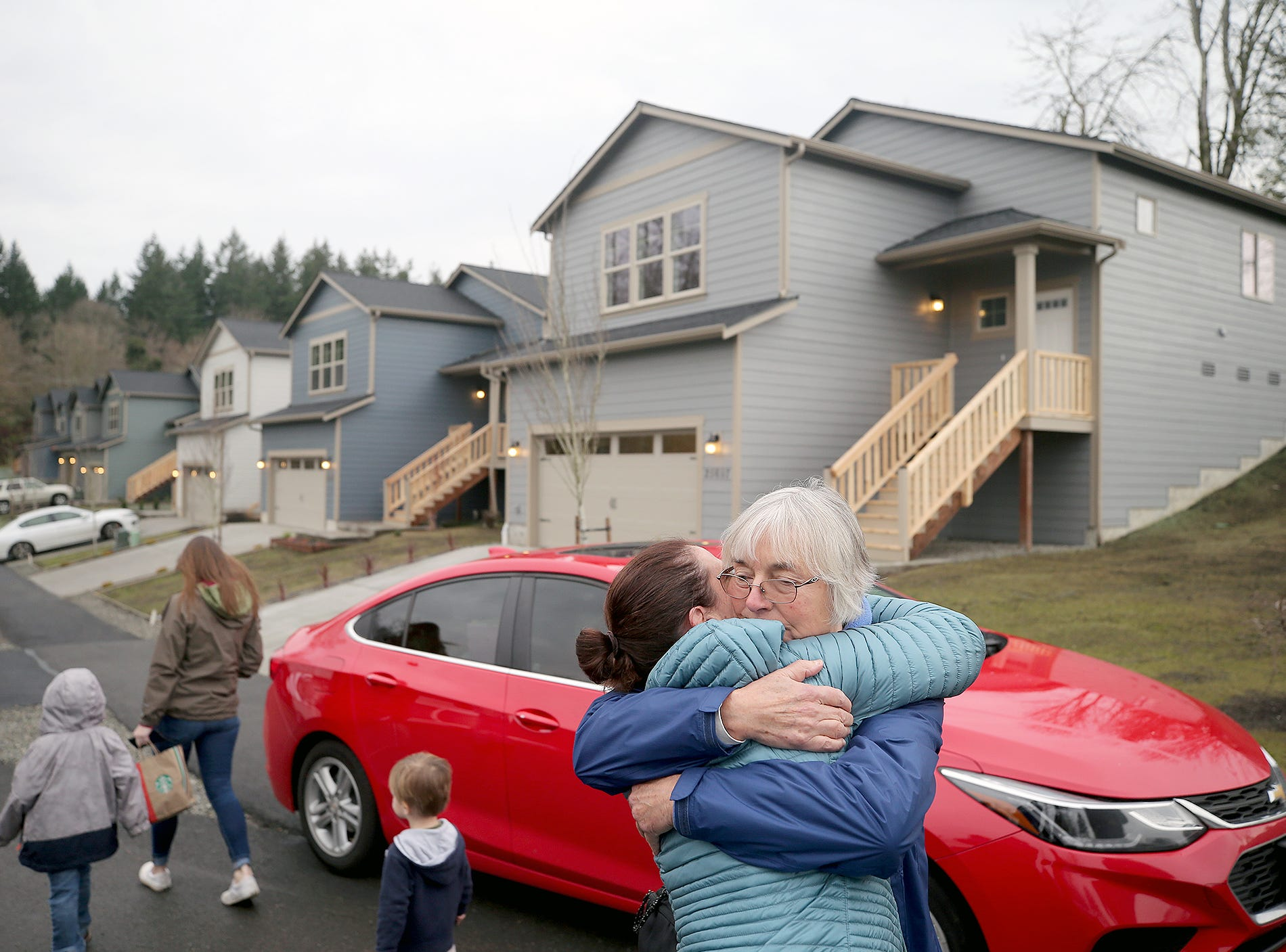 Ruby Moss of Bremerton gets a hug from Julie Buonacre of Bremerton at the opening ceremony of the Maple Lane Group One Kitsap Housing development in Kington on Friday, December 14, 2018. Her son Michael Porter was the construction superintendent on the site, they had a memorial for him because he tragically passed away last week.