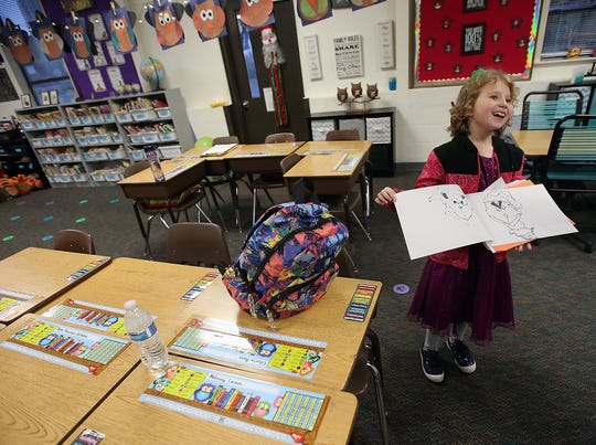 Gloria Bass, 8, shows her mother, Krystal Wallin, a drawing of the Grinch that she has been working on in her classroom at Olalla Elementary.