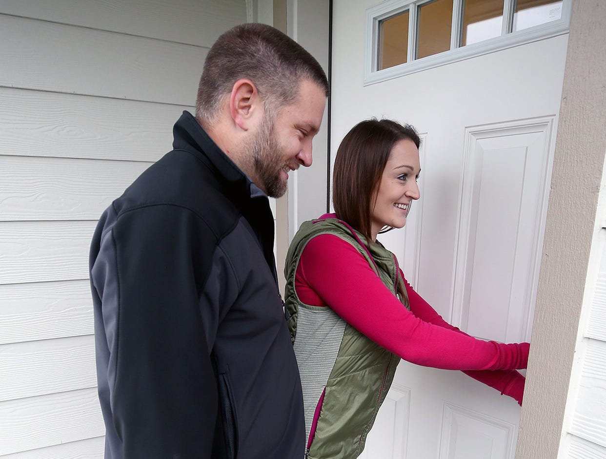 Brandon and Jessica Johnson unlock the front door to their new home at the opening ceremony of the Maple Lane Group One Kitsap Housing development in Kington on Friday, December 14, 2018.