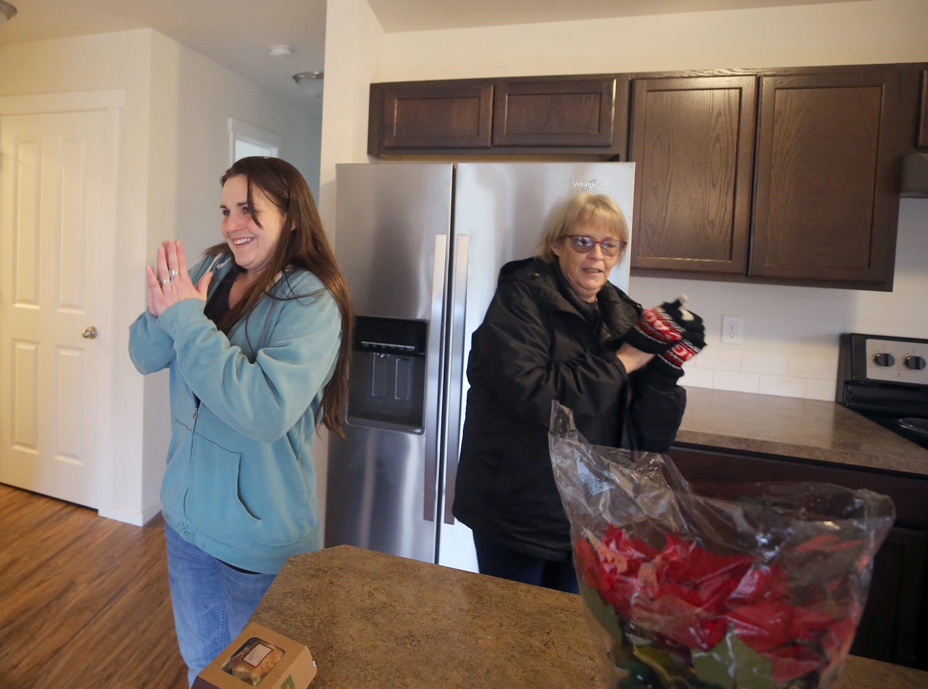 Elizabeth Stranberg is happy after going inside her new home after the Housing Kitsap at the opening ceremony of the Maple Lane Group One Kitsap Housing development in Kington on Friday, December 14, 2018. She is one of the new home owners.
