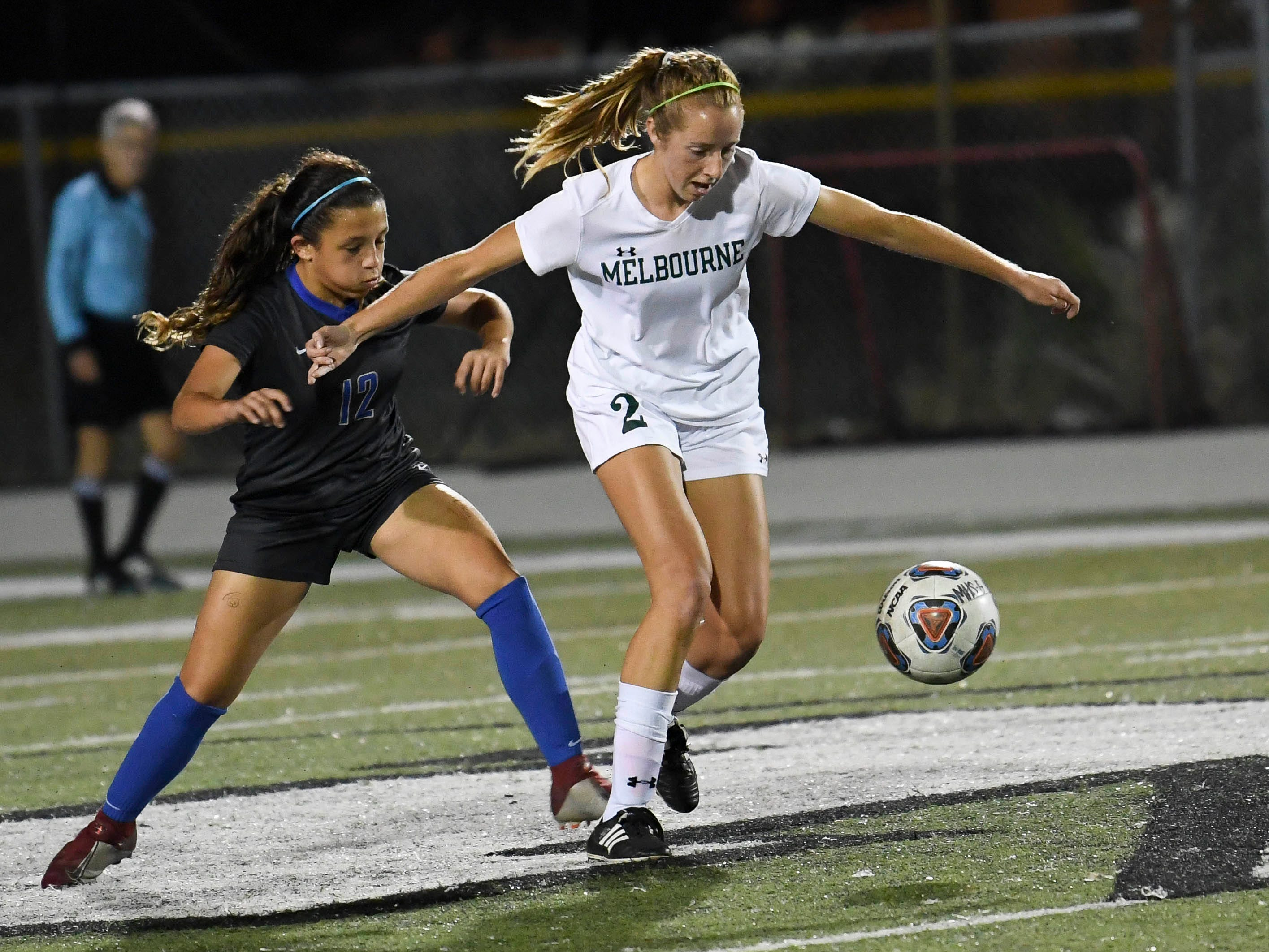Melbourne's Lindsay Baldwin battles with Barbara Garcia of Cypress Bay during Thursday's game in Melbourne