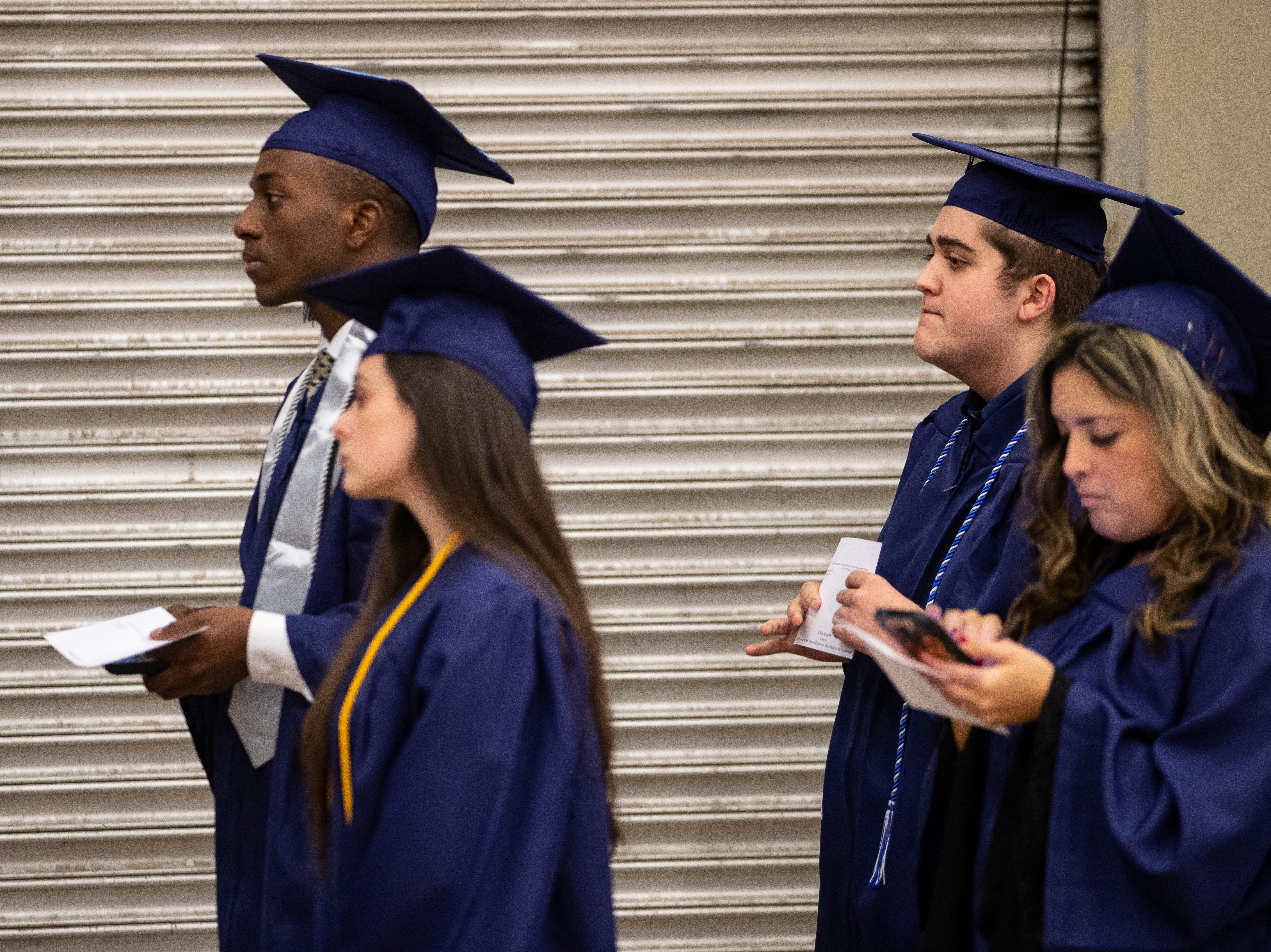 Flour Bluff's High School's Jeremiah Baldwin on his phone as he waits for the start of Del Mar's fall commencement ceremony on Thursday, Dec. 13, 2018.