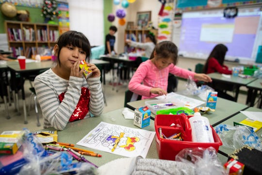 Banquete elementary school third grader Nylah Hernandez drinks a juice box at her desks from the nonprofit Be A Champion's dinner program on Friday, Dec. 14, 2018.