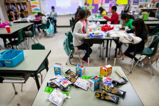Students in Mrs. Roan third grade class at Banquete elementary school eat food at their desks from the nonprofit Be A Champion's dinner program on Friday, Dec. 14, 2018.