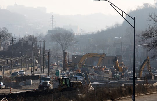 Construction crews work on Queen City Avenue, Monday, Dec. 10, 2018, in South Fairmount. The $90 million project will install a sewer line underneath a new park and green space. The project started in 2017 and will take until 2020 to complete.