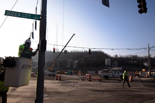 Construction workers rewire a stop light on Queen City Avenue, Monday, Dec. 10, 2018, in South Fairmount. The $90 million project will install a sewer line underneath a new park and green space. The project started in 2017 and will take until 2020 to complete.