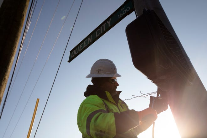 Construction workers rewire a stop light on Queen City Avenue, Monday, Dec. 10, 2018, in Fairmont. The $90 million project will install a sewer line underneath a new park and green space. The project started in 2017 and will take until 2020 to complete.