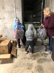 Volunteers Garrett and Jase Kring, along with Rita Brake, right, help unload a truck filled with toys following a shopping trip for Stewart County Children's Christmas Program.