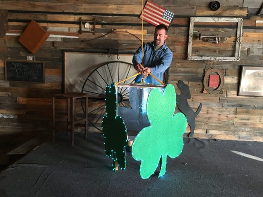 """Wes Mitchum attaches a three-sided shamrock to a winch he devised. """"The biggest challenge is making the timing just right,"""" he said."""