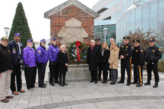 Freeholder Patricia Walsh, next to wreath, and Sheriff Frank Provenzano, at left, are joined by local veterans, county Veterans Office staff and Sheriff's Office representatives as a wreath from Wreaths Across America is placed at Veterans Memorial Plaza in Somerville.
