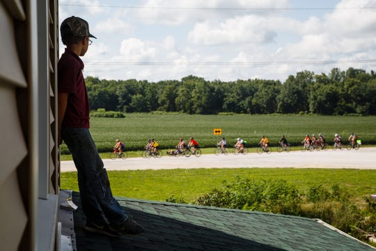 LaVern Miller, 12, watches cyclists on RAGBRAI make their way to Kalona, the meeting town of day six, on Friday, July 27, 2018.