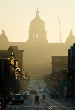 The sun rises over the Iowa State Capitol and Des Moines' East Village on Wednesday, March 28, 2018, in Des Moines.