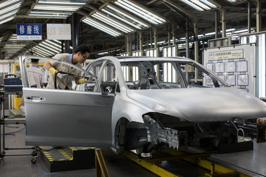 Employees work on the assembly line at the FAW-Volkswagen Automobile Co. plant in Foshan, Guangdong Province, China, in November 2018. FAW-Volkswagen Automobile Co., Ltd. is a joint venture between Chinese state-owned FAW Group and German carmaker Volkswagen Group. Audi and Volkswagen cars are manufactured there for sale in China.