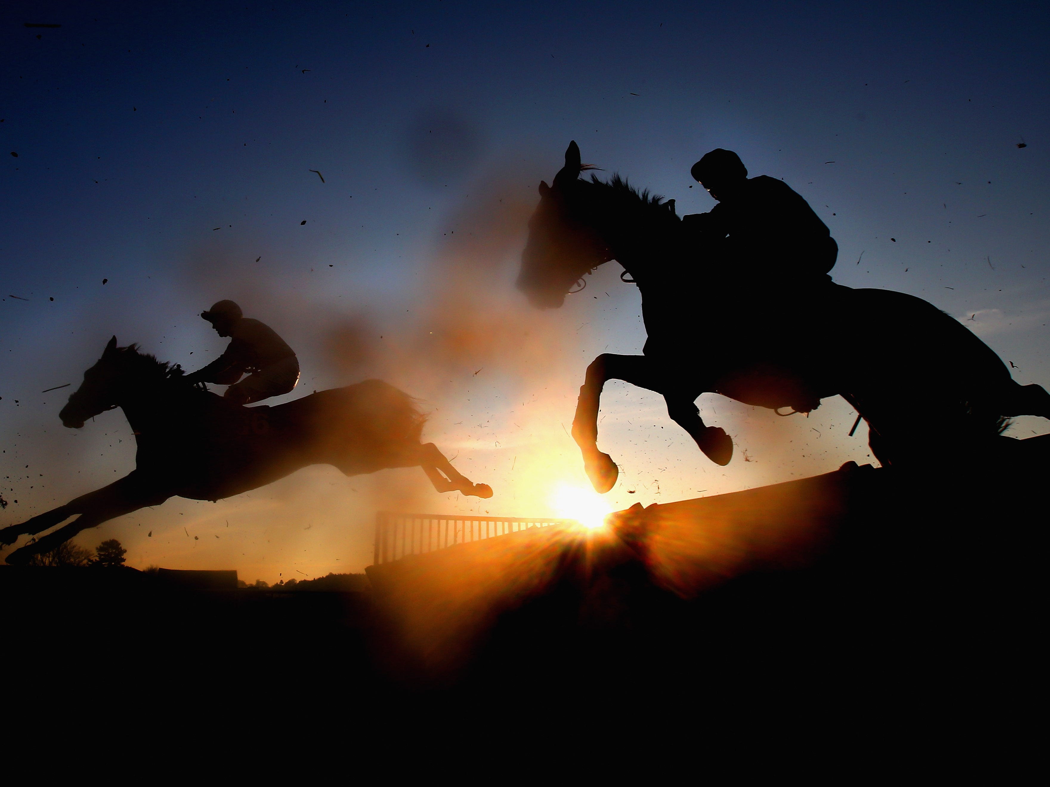 Horses and riders jump a fence during The Cliftons Of Wrexham Novices' Hurdle Race at Bangor Racecourse on Friday, Dec. 14, 2018 in Bangor, Wales.