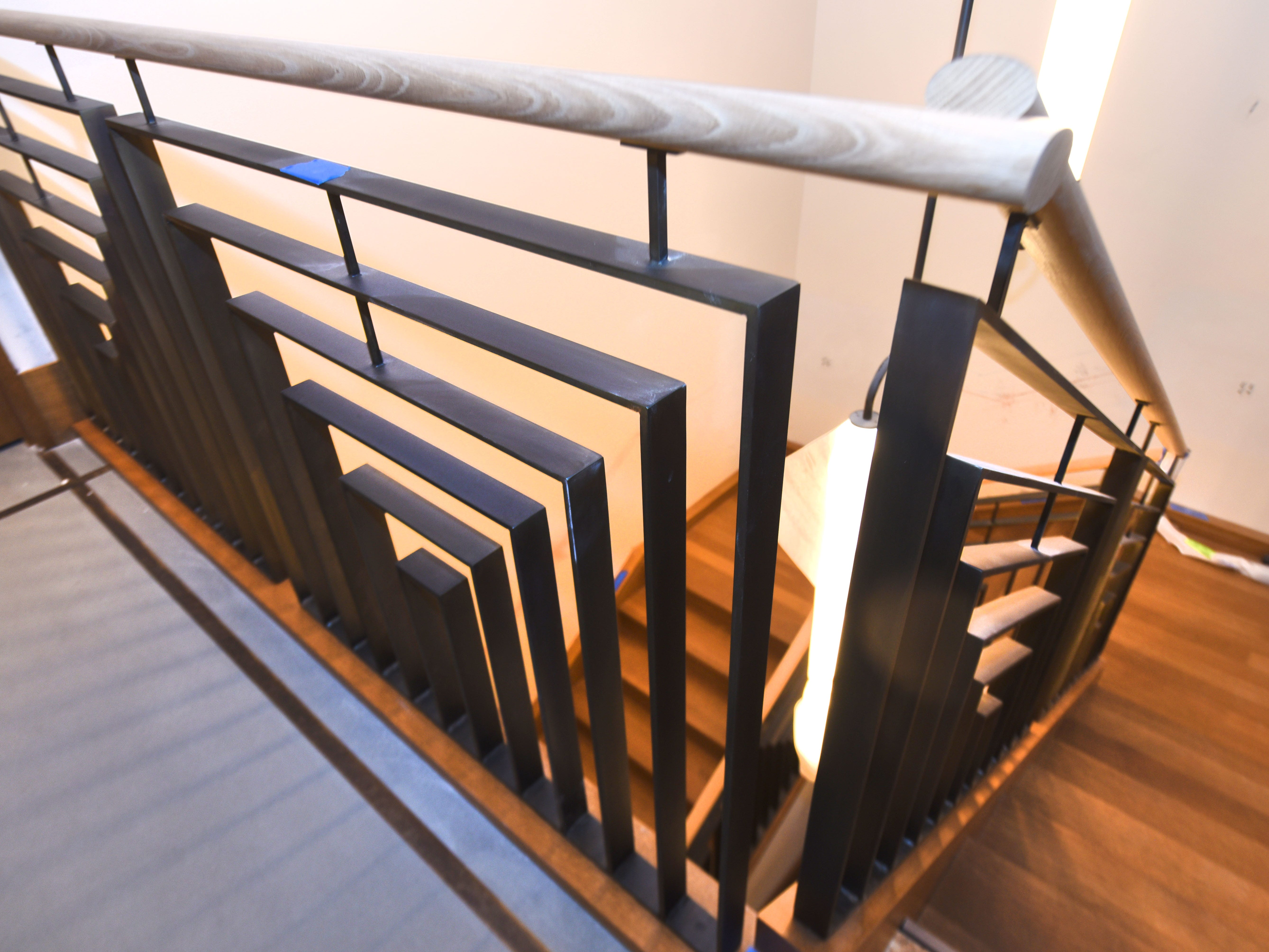 A steel and wood railing leads to the upper guest rooms.