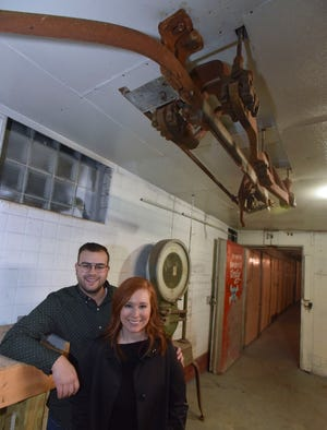 "Beatrice Wolnerman, 27, and her husband, Eli Wolnerman, 26, both of Grosse Pointe Farms, pose in front of a meat scale and polley system at their building in Eastern Market. They are renovating the former 1930s meat-packing building into a retail space, coffee bar, warehouse space and co-working membership business where they will also operate their businesses ""Open Me When"" and ""Bea's."""