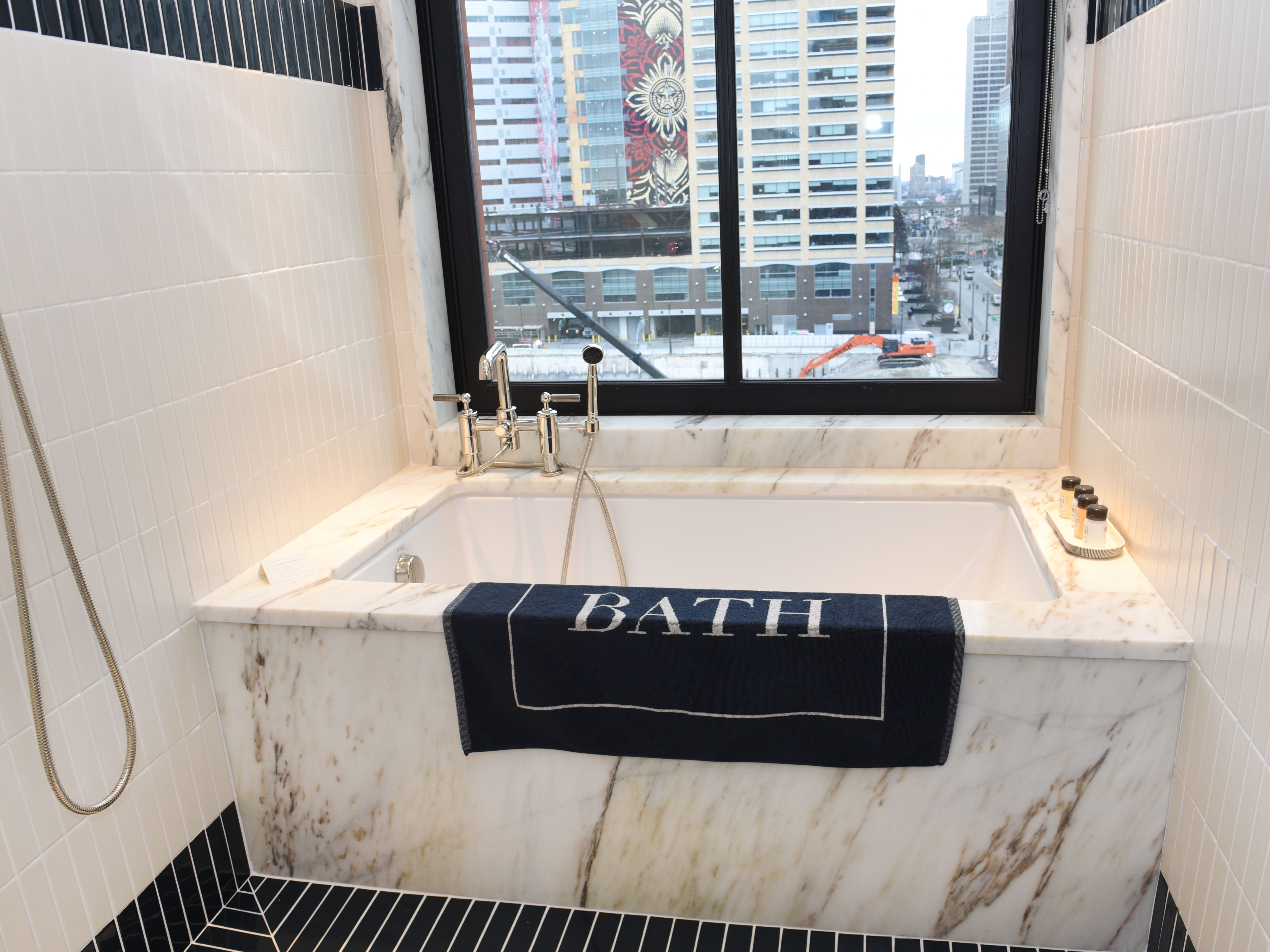 A bath tub and shower combination inside a guest suite.