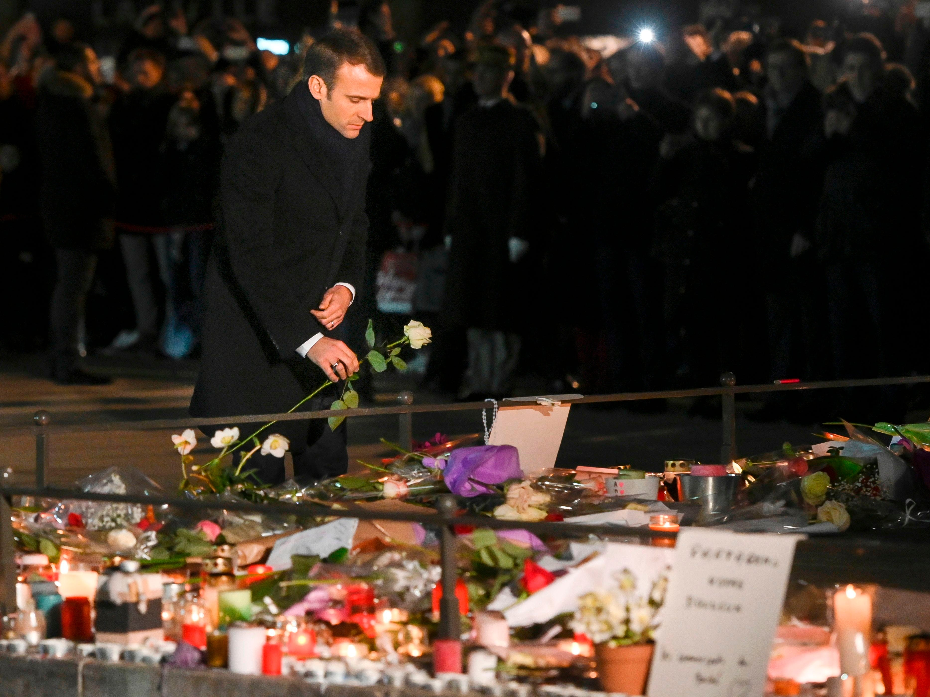 French President Emmanuel Macron lays a white rose at a monument near the Christmas market in Strasbourg, eastern France, used as a makeshift memorial for the victims of the Dec. 11 attack that killed four people.