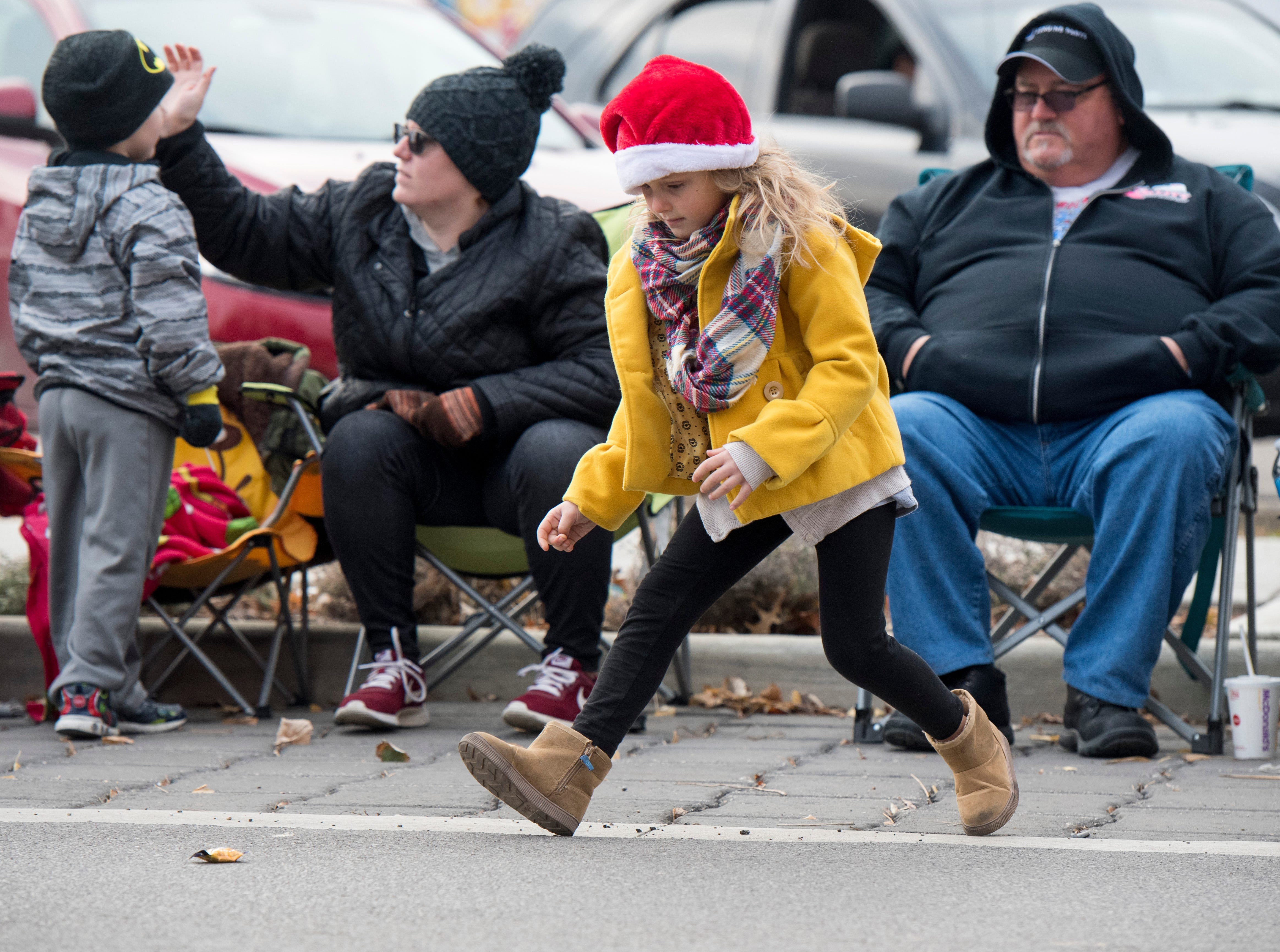 Lydia Brown, 6, runs after a piece of candy during Evansville's Christmas on North Main Parade, Sunday, Nov. 18, 2018.