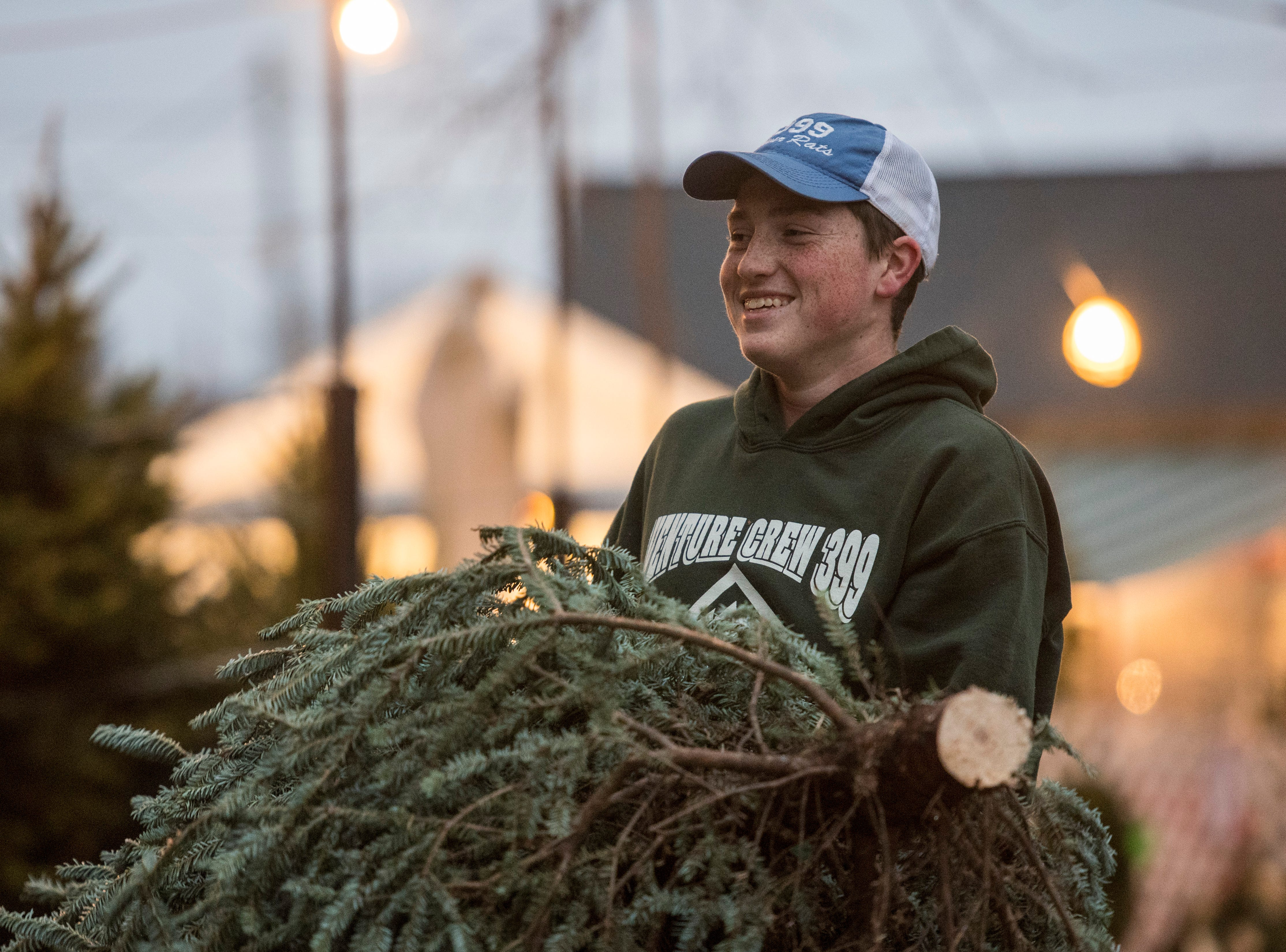 Larry Haller, 17, helps carry a Christmas tree for a customers while working at the Boy Scouts Troop 399 tree lot in front of Sacred Heart Catholic Church of the West Side, Thursday, Nov. 29, 2018.