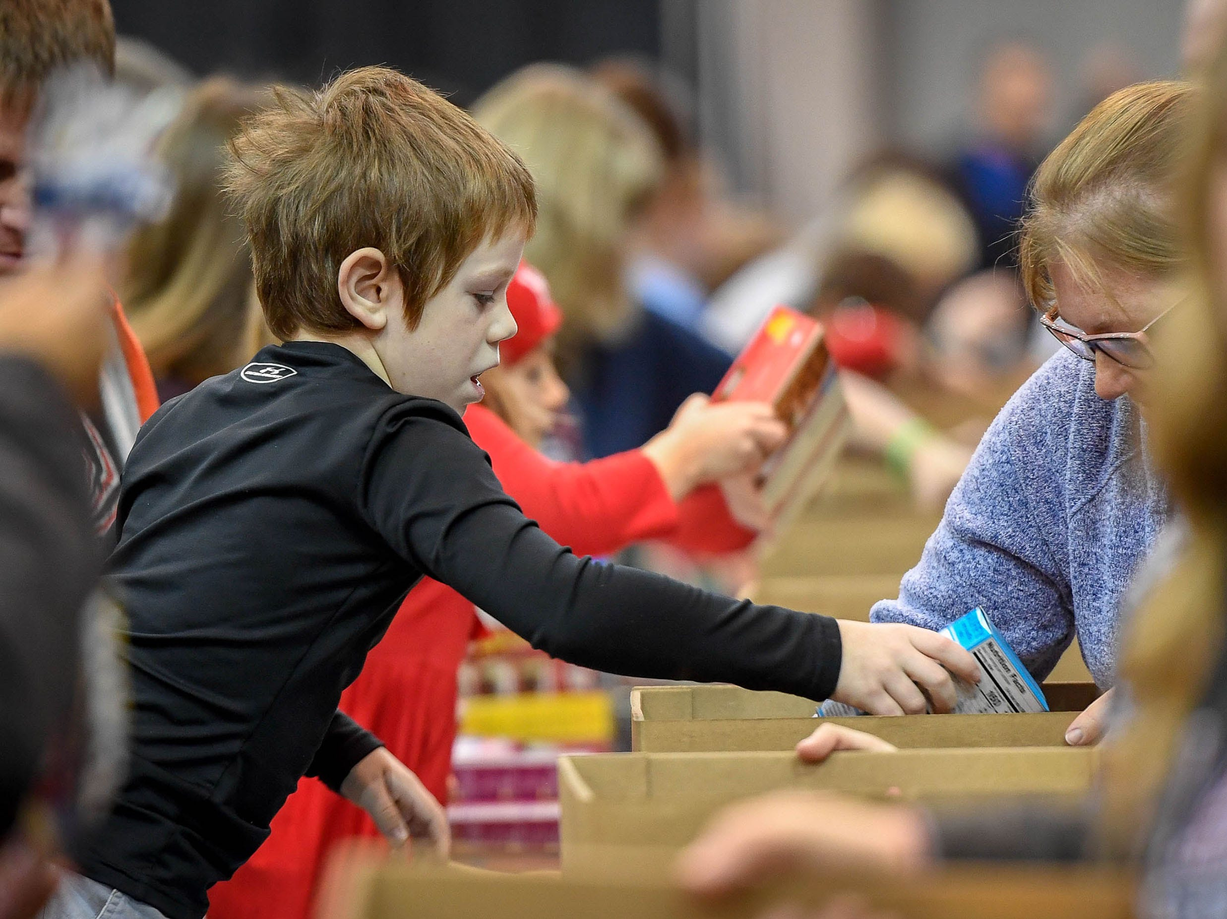 Doing his part, Carson Hetzel-Gaynor, 7, puts boxes of muffin mix into food boxes at the Evansville Rescue Mission's 96th annual Gobbler Gathering held at Old National Events Plaza, Tuesday, Nov. 20, 2018.