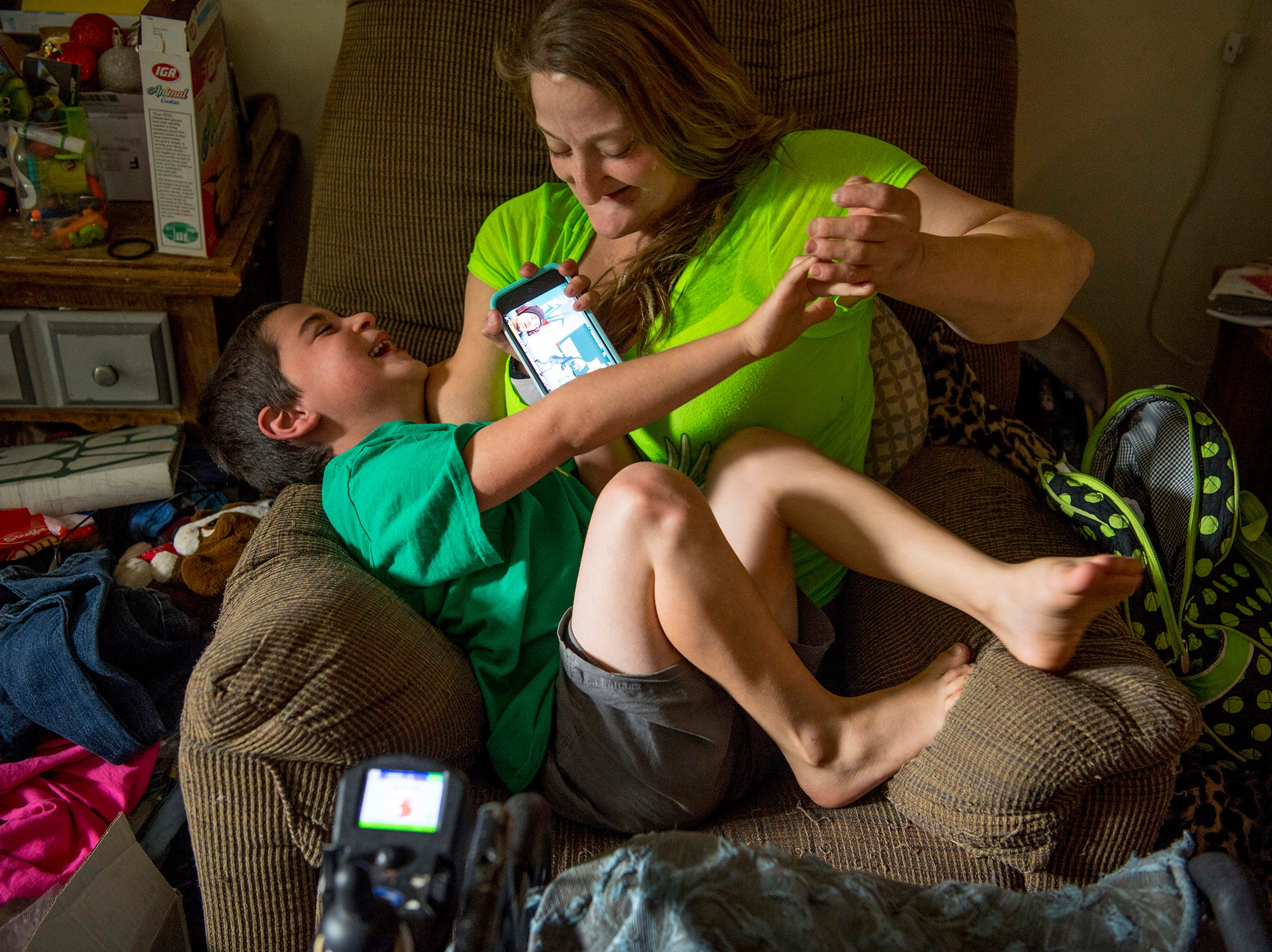 A tickle fight breaks out between Leland, 6, and his mother Amanda Smith as he tries to watch videos on her cell phone. This photo was included in a story published Wednesday, Nov. 21, about Amanda raising two children while dealing with a rare disease called Congenital Insensitivity to Pain with Anhidrosis.