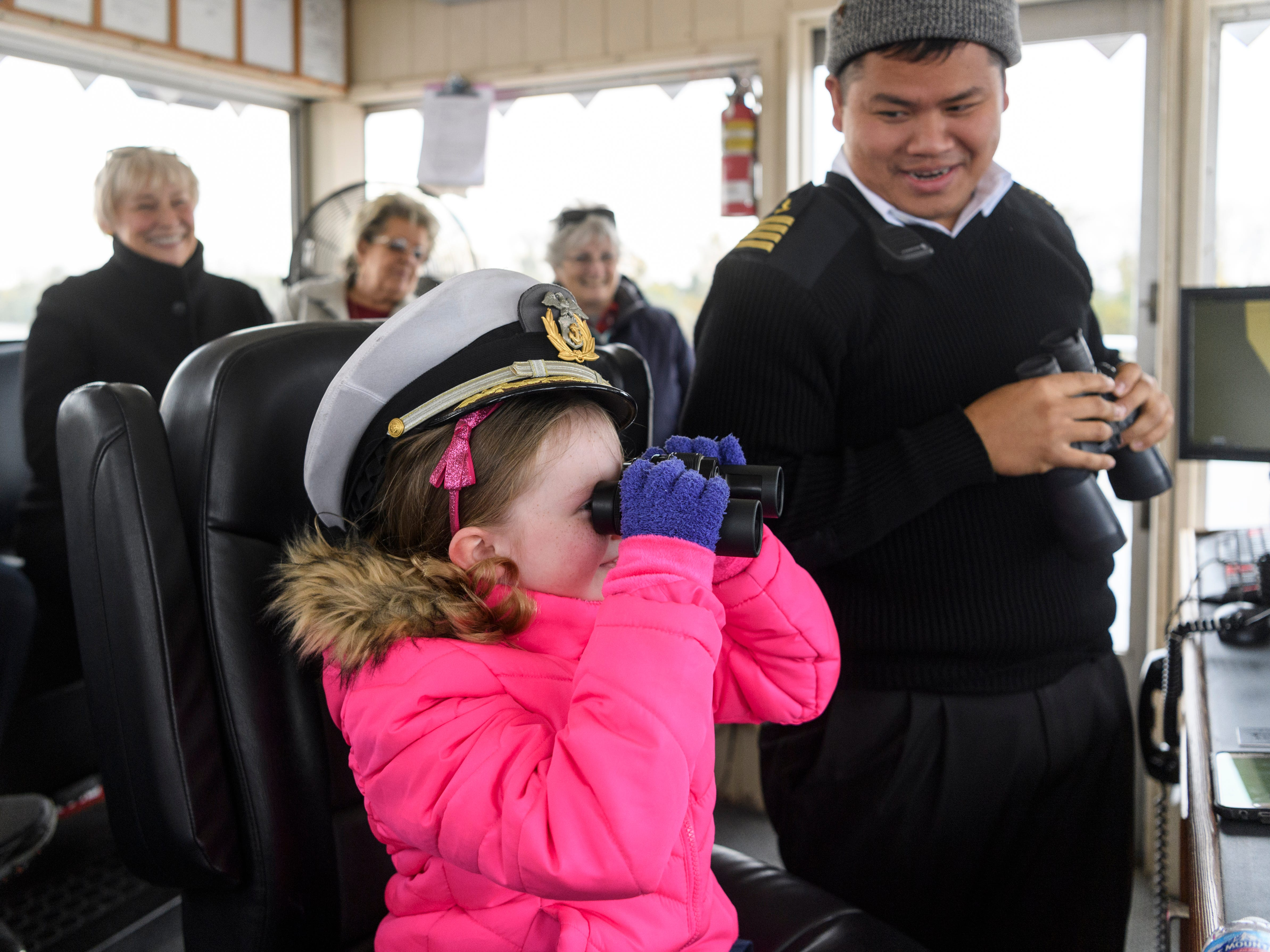 Daniela Meeks, 7, helps Captain Sam Sengsouvanh, right, steer the Belle of Cincinnati during a two-hour lunch cruise along the Ohio River near Henderson, Ky., Thursday afternoon, Nov. 8, 2018. Over 230 people climbed aboard the ship in downtown Henderson for food, drinks, dancing and sightseeing.