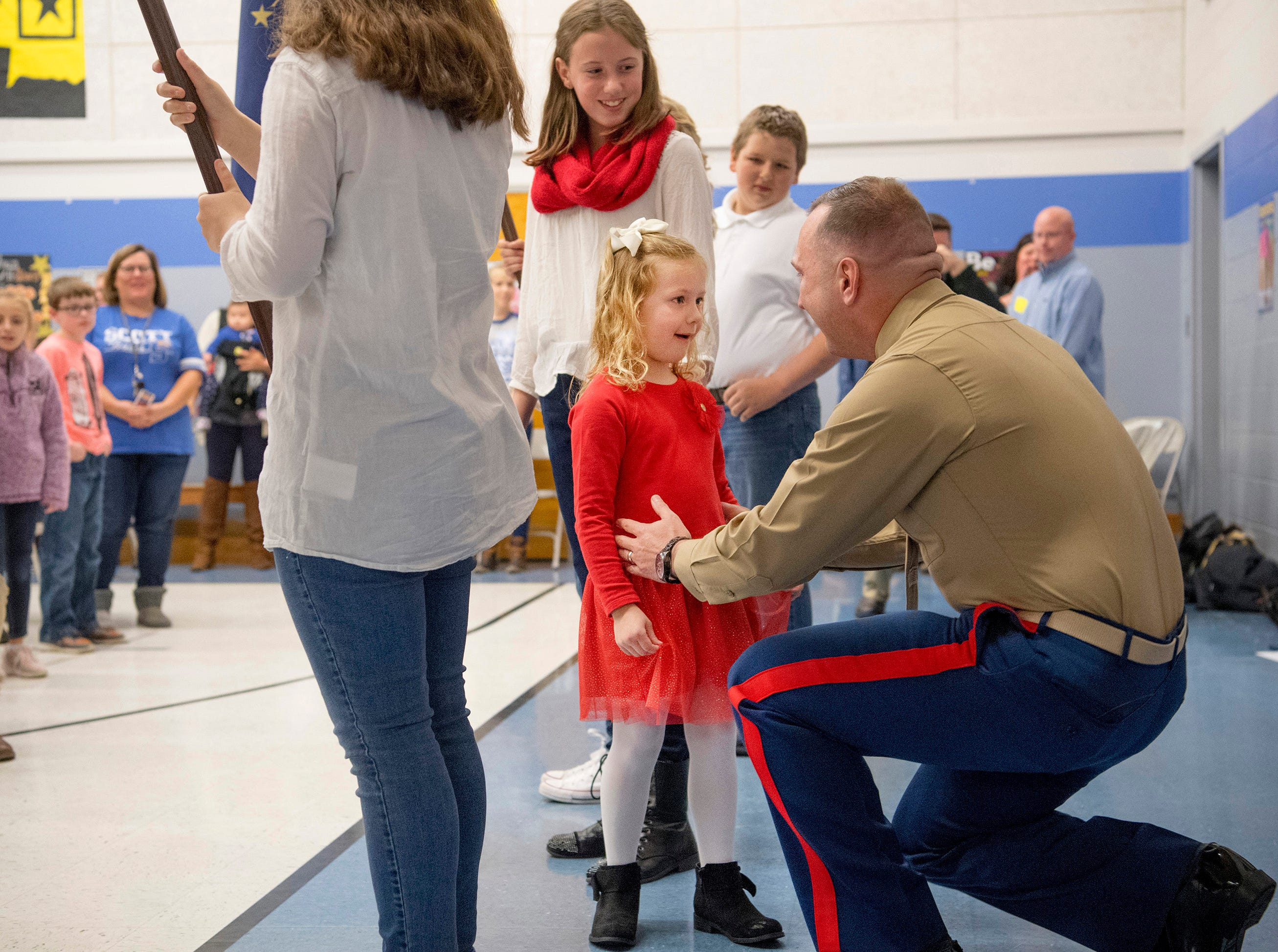 Scott Elementary School kindergartner Eliana Marzec, 5, center, is surprised to find her father, Marine Corps Capt. Ryan Marzec, standing behind her during the Veterans Day program Friday morning, Nov. 9, 2018. Captain Marzec returned from a tour in Afghanistan and surprised the eldest of his three daughters.