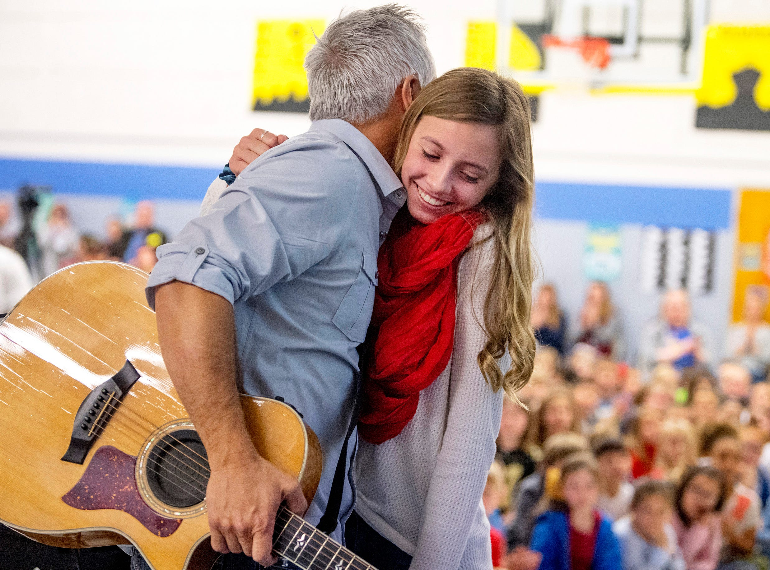 "Gracie Winzinger gives her dad, Scott Winzinger, a hug after he played ""God Bless the U.S.A."" by Lee Greenwood at Scott Elementary School's Veterans Day program Friday morning, Nov. 9, 2018."