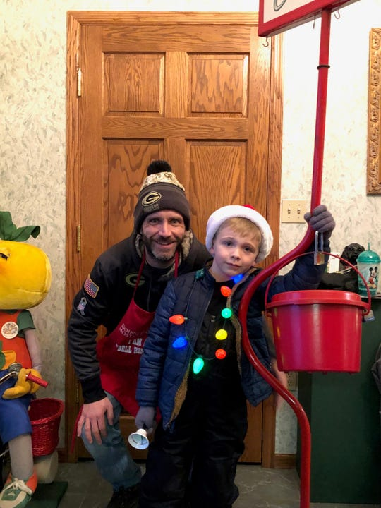 Finley Cardinal and his dad Kurt Cardinal pose in front of a red kettle.  Lisa Cardinal, Finley's mom, is the daughter of Bill Mongin, one of the local individuals matching donations for the Red Kettle Campaign.