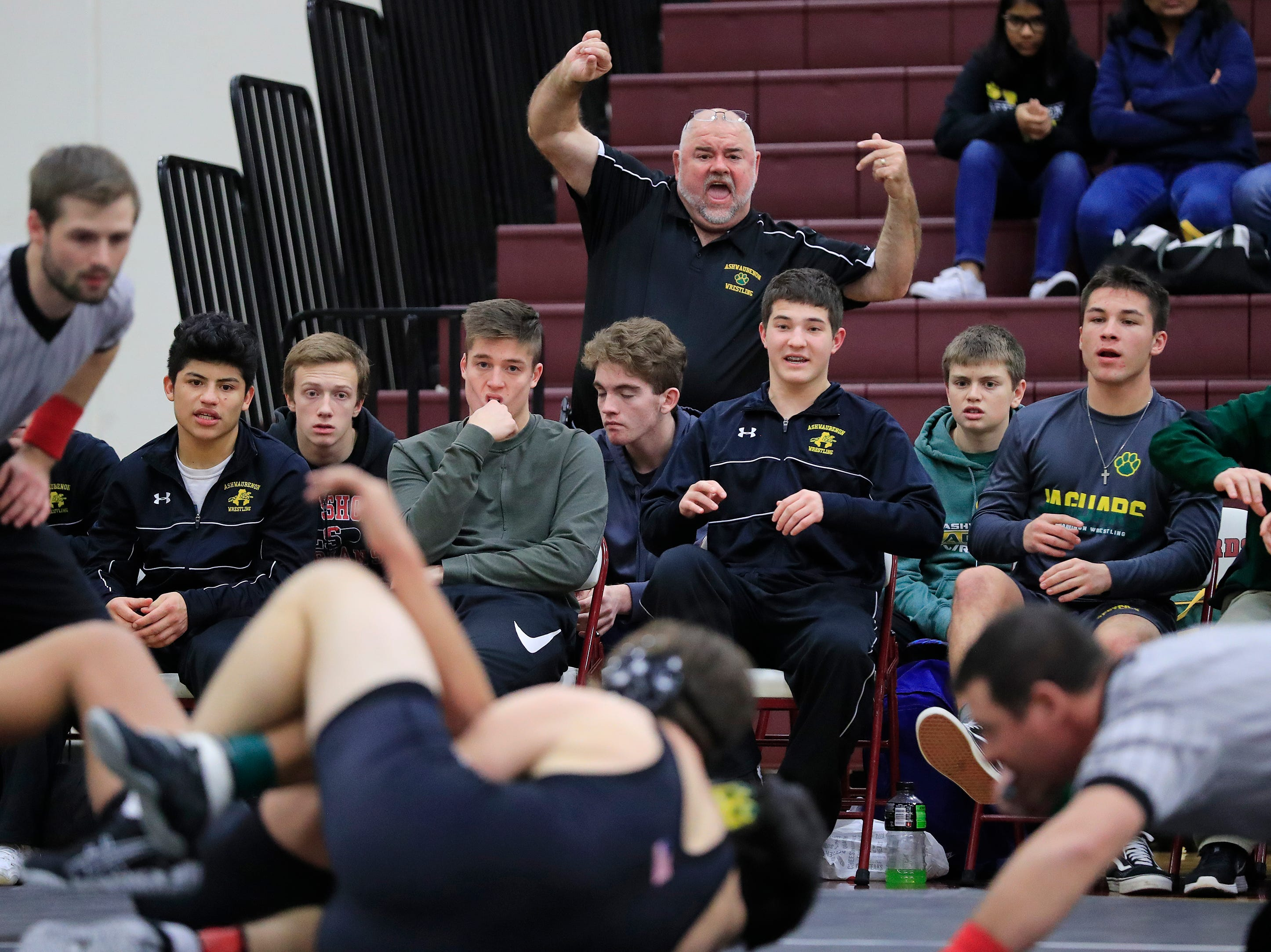 The Ashwaubenon bench reacts during a wrestling meet at De Pere high school on Thursday, December 13, 2018 in De Pere, Wis.