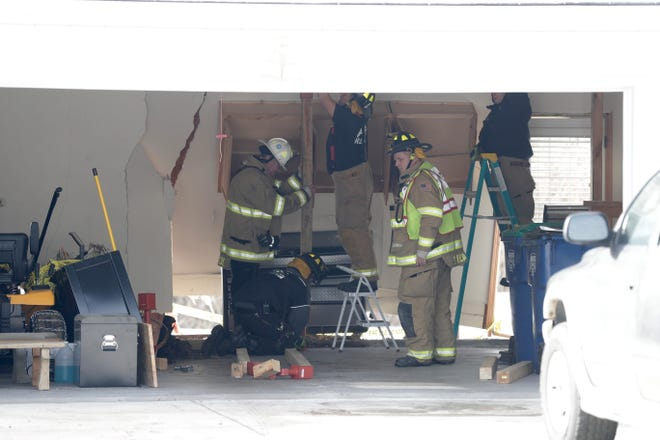 Bellevue firefighters work inside a garage at 3242 Meadow Circle trying to shore up a wall that was damaged when a driver lost control of her car.