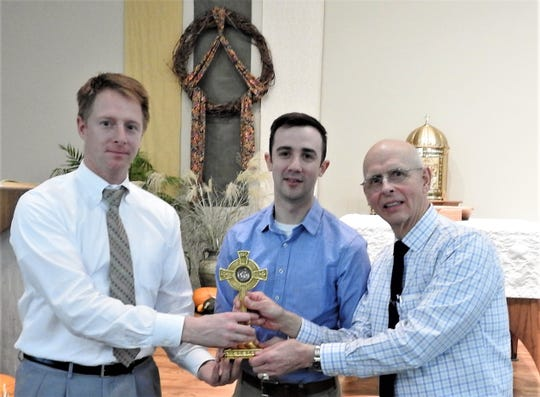 From left, St. Anthony School principal Alex Wolf, Green Bay Diocese Director of  Divine Worship Michael Poradek and parish member J.R. Ryczkowski hold a cross containing relic of St. Anthony.  Poradek and Ryczkowski assisted in its acquisition.