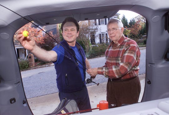Jack Tate, left, checks over his uncle's fishing gear Nov. 19, 2002, in the back of his uncle's vehicle. His uncle, George Tate, went fishing early morning and stopped by his nephew's home in the afternoon to talk about his exploits. George Tate died in 2015.