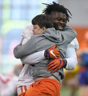 Clemson defensive lineman Albert Huggins (67) hugs equipment manager David Saville during the Tigers Cotton Bowl practice on Friday, December 14, 2018.
