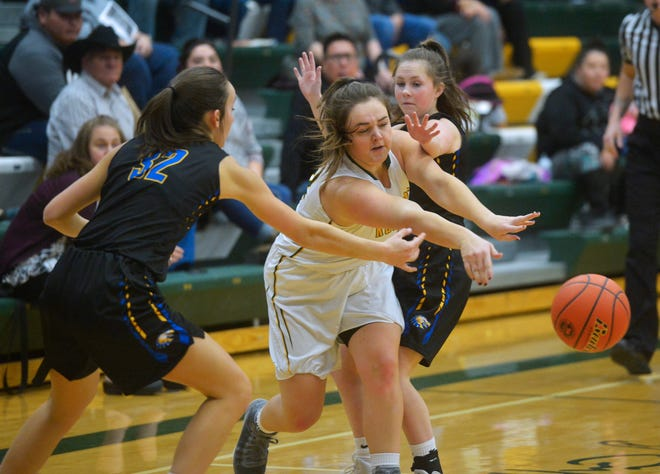 CMR's Marley Calliham makes a pass between Missoula Big Sky defenders Demi Smith, left, and Corbyn Sandau during Thursday evening's baskeball game in the CMR Fieldhouse.