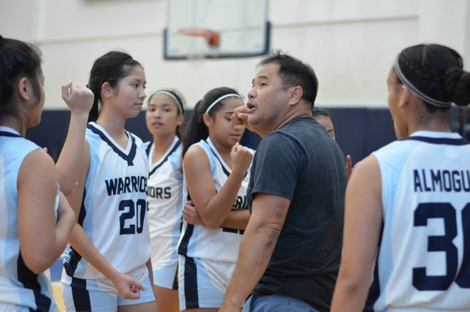 St. Paul Christian Warriors junior varsity girls basketball head coach Neo Pineda takes a timeout during a game in early November. The team finished the season unbeaten at 15-0 to claim the 2018 title.