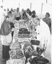 """An undated photo depicts a traditional CHamoru fiesta table. From the original caption: """"Father Tim, Bishop Flores and guests enjoy a feast prepared by the people of Talofofo after the joint celebration."""