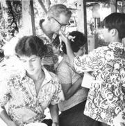 In this undated photo, Tommy Mendiola of Mongmong holds out a Niñu Jesus figurine. Taking part in the Catholic tradition are Paul Kuntz of Yigo (center), Marie Kuntz and Paul Kuntz, Jr.