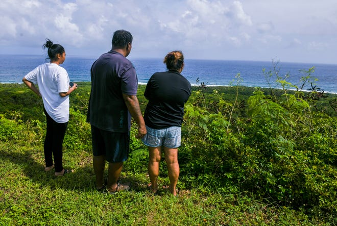 Inarajan resident Kin Taimanglo, center, and other family members watch as a Guam National Guard aircrew, operating a UH-72A Lakota light utility helicopter, descends to pick up his close friend and the missing crab hunter, Michael Guerrero, along the shoreline below at Asiga, Malojloj, on Friday, Dec. 14, 2018. Guerrero, 45, was reportedly found in a tree found by personnel searching for him at about 10 a.m. that morning. Guerrero was hoisted into the helicopter and transported to the Naval Hospital Guam, according to Guam Fire Department firefighter and spokesman Kevin Reilly.